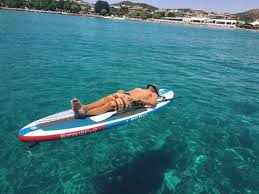 man resting on a paddleboard over a reef